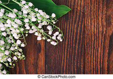 Background of brown wooden boards with forest flowers lilies of the valley. Tint photo with space for text