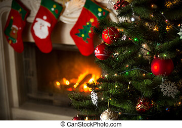 Background of Christmas tree at living room with burning fireplace decorated with traditional stockings for gifts