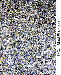 Background of colored pebbles in cement wall.