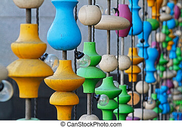 Background of different colorful wooden shapes and light bulbs outdoors
