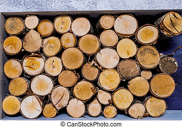 Background of dry chopped firewood logs stacked up on top of each other in a pile. Fuel wood, wood for fireplace, in the background of the wood burning stove, fireplace.