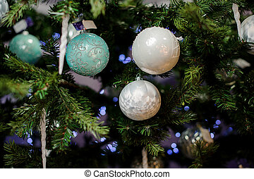 Background of evergreen fir tree with different colors bulbs