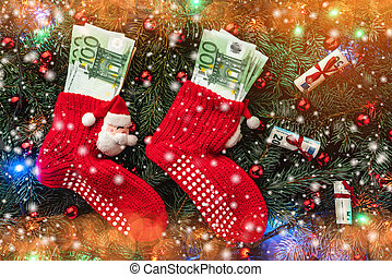 Background of fir branches. Santa's red stockings with money. Christmas card. Top view. Xmas congratulations. Lights. Effect snowflakes.