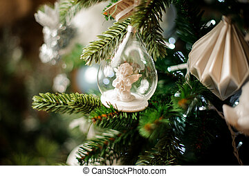 Background of fir tree with toy little angel white christmas decoration