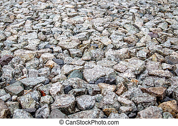 Background of gray stones at a road repair construction site as a drainage layer for paving asphalt