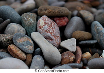 Background of large grey pebbles on beach