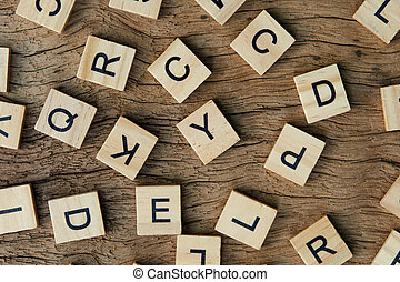 background of letterpress wood type printing blocks on wooden background, random letters of alphabet and punctuation stained by black inks