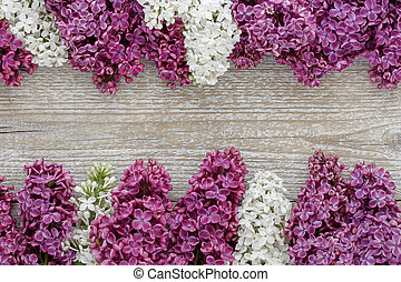 Background of lilac flowers on a wooden surface