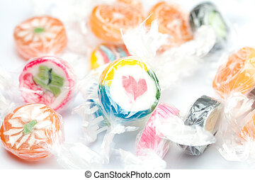 background of multi-colored candies in shiny wrappers