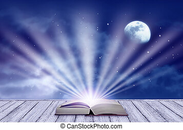Background of night sky with mysterious clouds, moon, stars and open fairytale book and rays shining from it on table