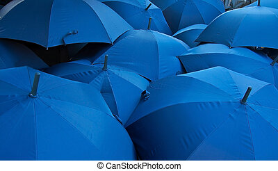 background of open blue umbrellas receding into distance