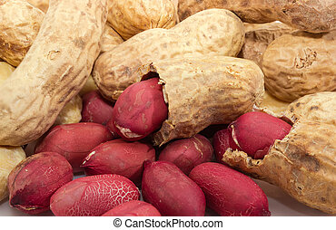 Background of partly peeled roasted peanuts close-up