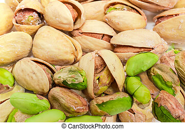 Background of partly peeled roasted salted pistachio nuts closeup