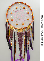 Background of purple dreamcatcher macrame feathers on gray wall