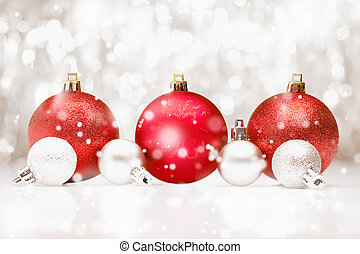 Christmas baubles in falling snow - Background of red ...