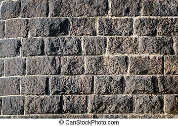 Background of stone wall texture photo with a brick in sunlight