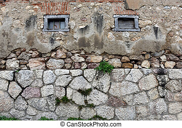 Background of stone wall with small wooden windows