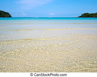 Background of transparent crystal blue sea water surface ripple over sand with sun reflection in summer. Water background. Ocean water texture.