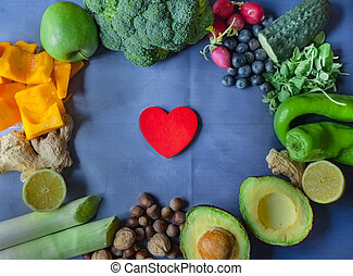 Background of vegetables, fruits and nuts with red wooden heart