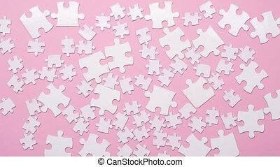 Background of white dancing puzzle pieces on pink background