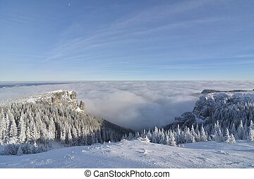 Background photo of low clouds in a mountain valley, vibrant blue and orange sky.