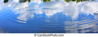Disturbance in the Yahara River causes a ripple to grow on its' surface. Vivid blue sky and fluffy clouds reflect on smooth surface.