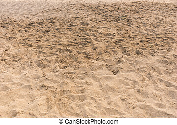 Background texture of golden beach sand with footprints and...