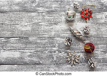 Background with a border of  Christmas decorations and white painted pine cones on  gray wooden table. Space for text.