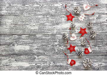 Background with a border of red Christmas decorations and white painted pine cones on  gray wooden table. Space for text.