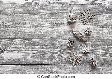 Background with a border of silver Christmas decorations and white painted pine cones on  gray wooden table. Space for text.