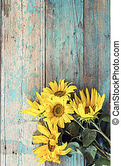 Background with a bouquet of yellow sunflowers on old wooden boards with peeling paint.