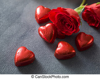 Background with chocolate hearts and red roses