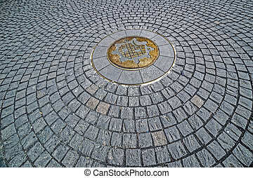 Background with cobblestone having in the middle the symbol of Timisoara, Romania