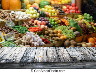 Background with empty wooden table and blured fruits and vegetables