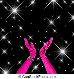 Black background with elegant arms extended while clapping in air - fuchia long sleeve gloves and white star-like flares
