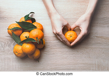Background with hands holding tangerines. Winter holiday frame. Flat lay top view