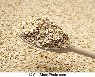 Background with oat flake in a wooden spoon