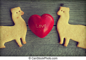 Background with sugar cookies shaped as ferrets on a wooden table background with little red heart, love background