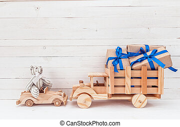 Background with vintage toys: wooden car with teddy bear and wooden truck with gifts.