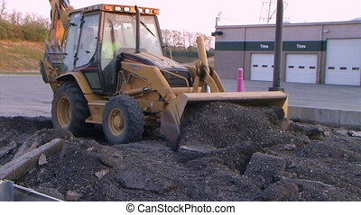 Backhoe Loader Pushing Pavement - Backhoe loader works to...