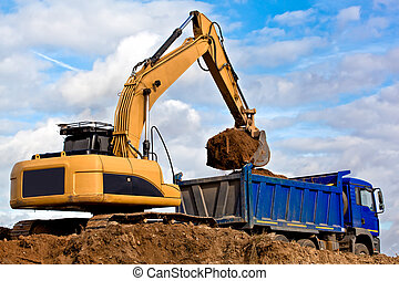 Excavator loading a dump truck at construction site