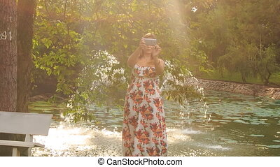 Backlight Blond Girl Turns around Makes Selfie in Park by Fountain