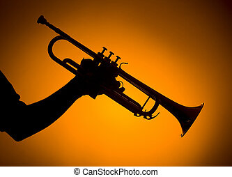 backlight hand holding trumpet on orange background