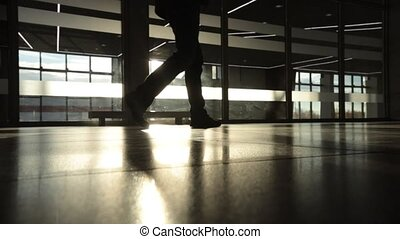 backlight silhouette of mystery man walking in front of big window