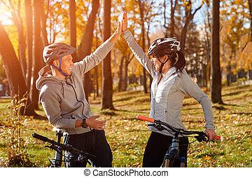 backlight., vélo, couple, avoir, ensoleillé, jeune, jour, automne, park., amusement, équitation, attrapé, heureux