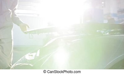 Backlight view of hood for the luxury sport car - mechanic in automobile garage