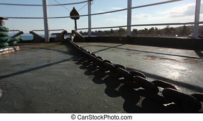 Backlit at ship deck on sunny day with chain for anchor -...
