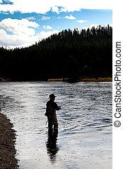 backlit fly fisherman in river