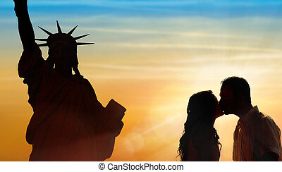 Backlit loving couple honeymoon in New York with liberty...