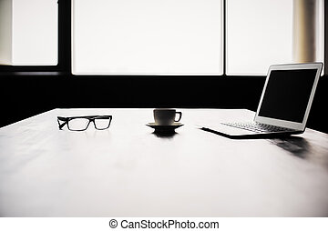 Backlit office desktop with blank laptop screen, coffee cup...